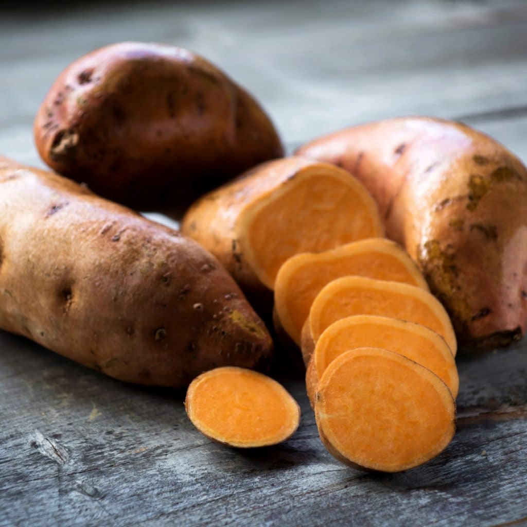 Raw sweet potatoes on wooden background closeup