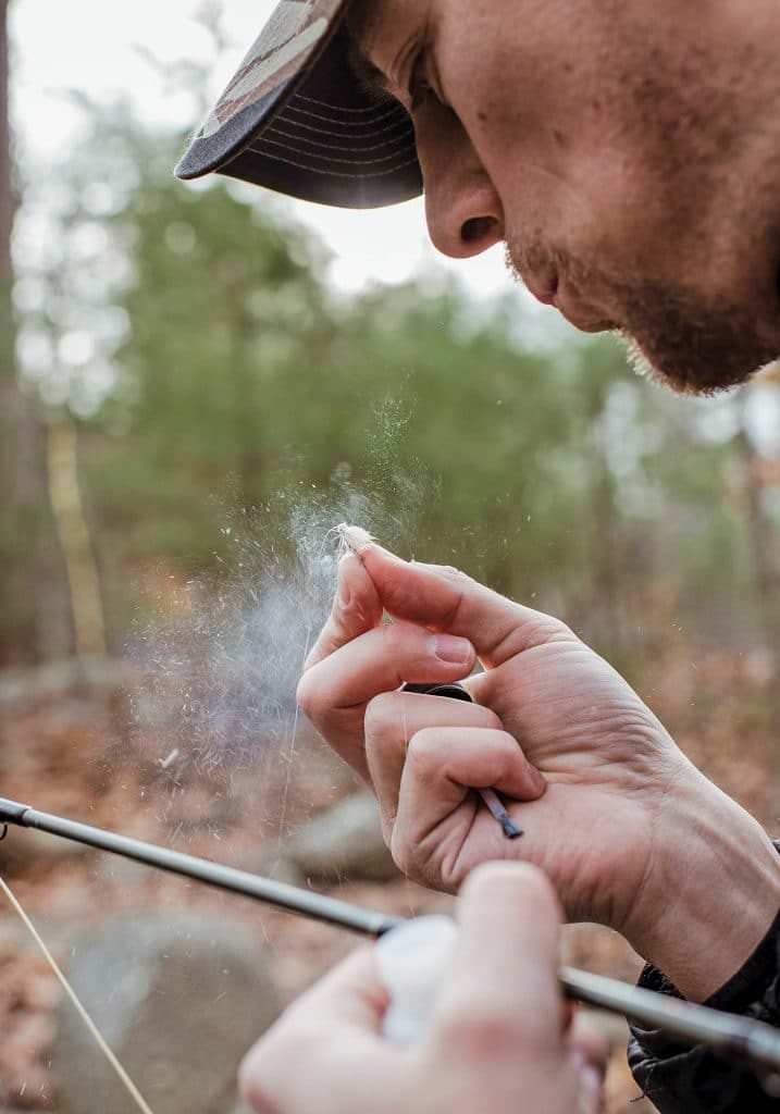 Man blowing on fly fishing bait