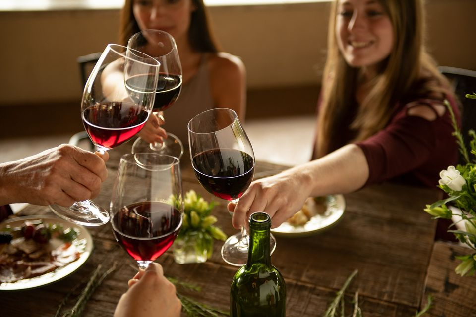 People enjoying red wine and food